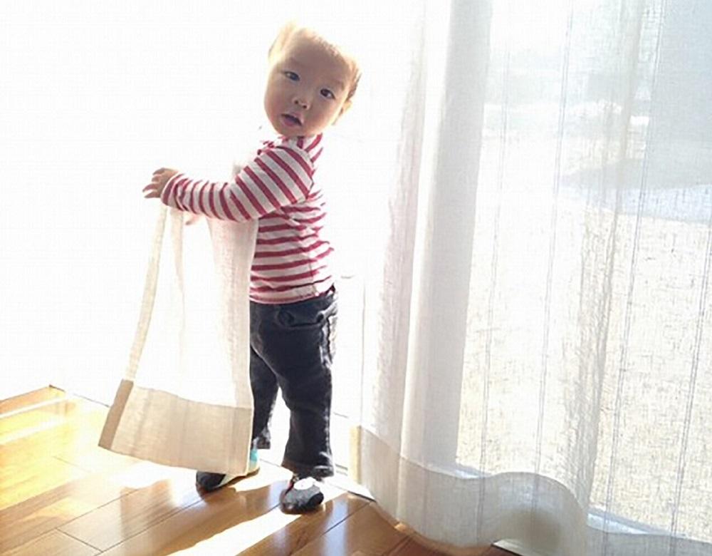 Lif/Lin(リフリン)リネンのオーダーカーテン カーテンと戯れる子どもの写真