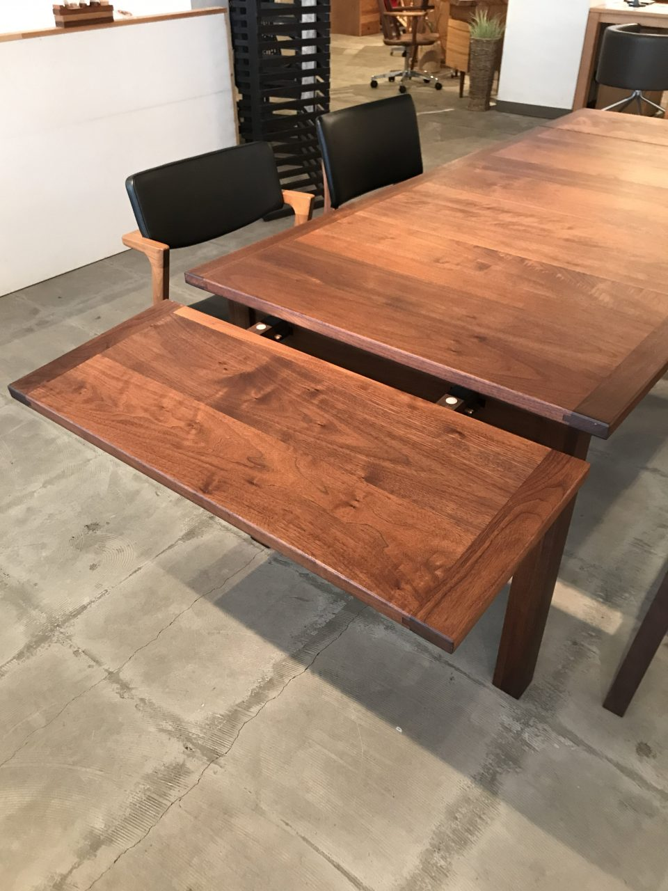 伸長式のウォールナット材のダイニングテーブルは天板がスライドして大きくなります