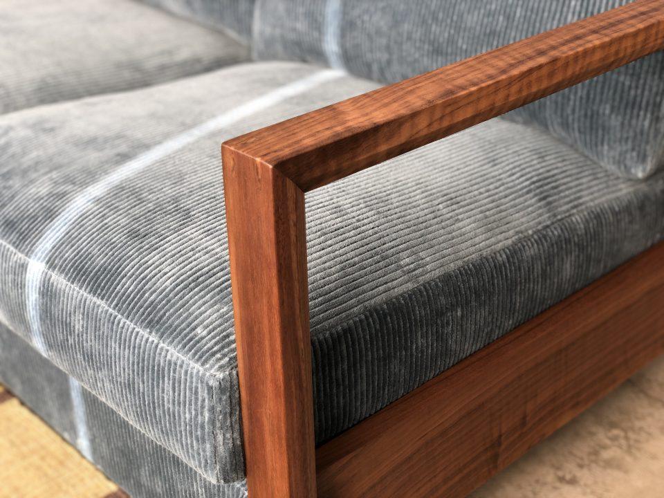 ウォールナット材の木肘のカウチソファが、コーデュロイの張地でおしゃれです