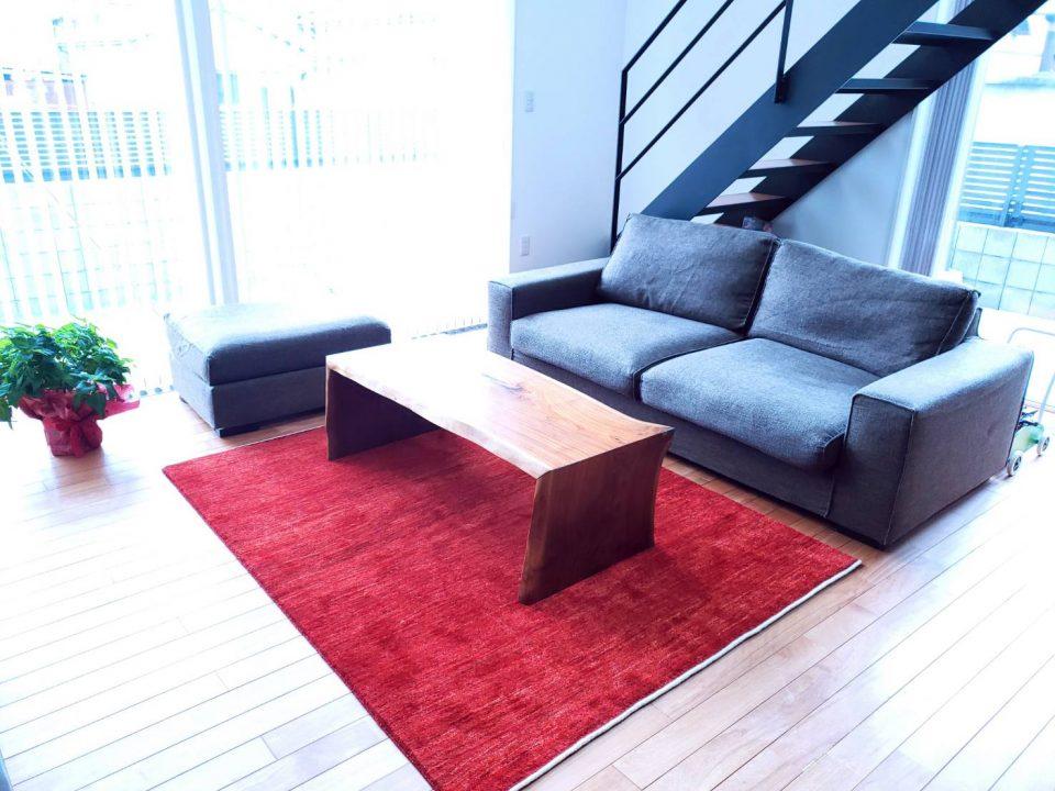 茜色の絨毯の上に一枚板のリビングテーブルが置いている様子