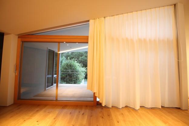 傾斜窓にカーテンを付けているスタイル